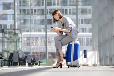 Portrait of a smiling business woman looking at mobile phone and sitting on suitcase waiting at the airport Фото со стока