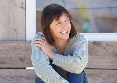 woman relaxing: Close up portrait of a natural older lady smiling outside Stock Photo