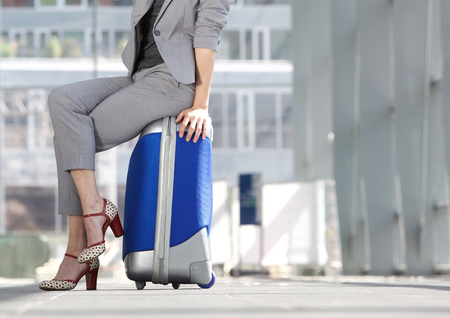 waist down: Waist down business woman sitting on suitcase at airport Stock Photo