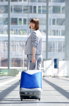 turn away: Full body portrait of a happy traveling business woman walking away with bag