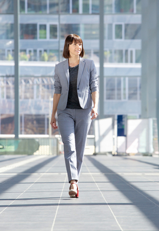 Full body portrait of an attractive professional business woman walking