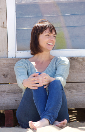 mid adult women: Portrait of a happy middle aged woman in jeans sitting outside Stock Photo