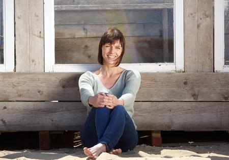 mujer sentada: Retrato de una encantadora mujer mayor que se sienta afuera