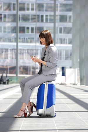 return trip: Portrait of a smiling business woman sitting on suitcase with mobile phone