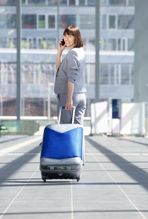 persona caminando: Retrato de cuerpo entero de una mujer de negocios a pie con bolsa de viaje y el teléfono móvil