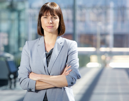 Close up portrait of a serious business woman in gray suit standing in the city Standard-Bild