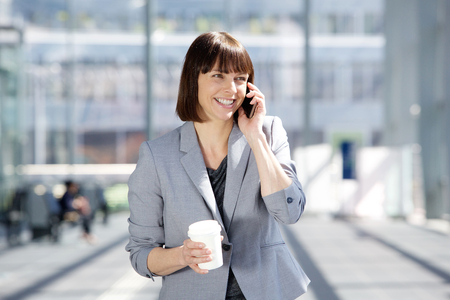 Close up portrait of a happy business woman walking and talking on cell phone while holding cup of coffee photo