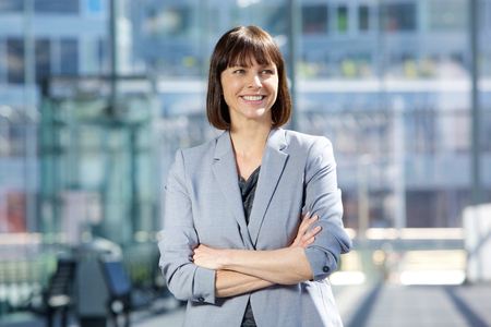 Close up portrait of an attractive business woman smiling with arms crossed in the city photo