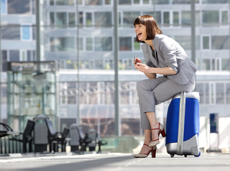 Side portrait of a business woman sitting on suitcase and laughing with mobile phone photo