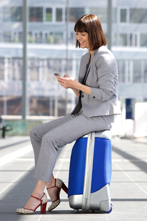 return trip: Portrait of a happy business woman sitting on suitcase at airport with mobile phone