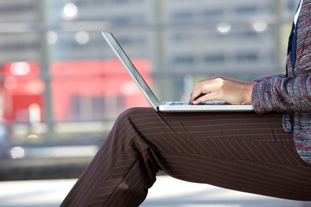 adult  body writing: Side portrait of a woman typing on laptop outside Stock Photo
