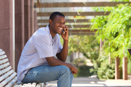 cell telephone: Portrait of a smiling black guy talking on mobile phone outside