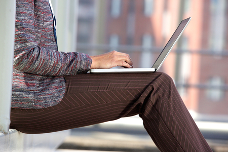 adult  body writing: Side portrait of a business woman typing on laptop outside