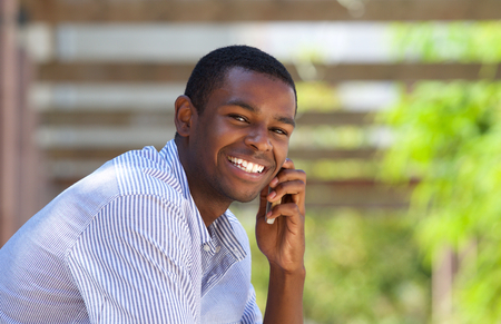 Close up portrait of a smiling black guy using mobile phone outside Banque d'images