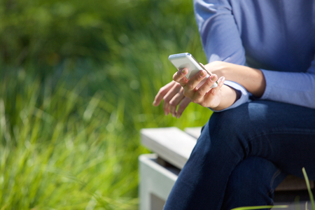 text space: Close up female hands using cell phone in the park Stock Photo