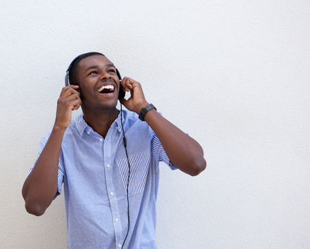 african man: Portrait of a happy african american teen listening to music with headphones Stock Photo