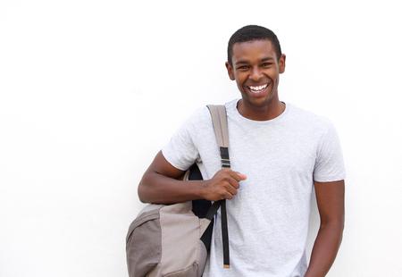 jovenes estudiantes: Retrato de un estudiante universitario sonriente con el bolso en el fondo blanco Foto de archivo