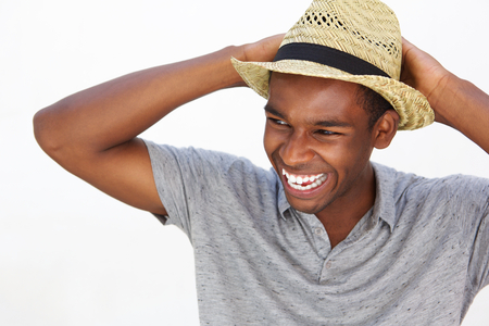 hombre con sombrero: Close up retrato de un hombre afroamericano despreocupado y sonriente con sombrero sobre fondo blanco Foto de archivo