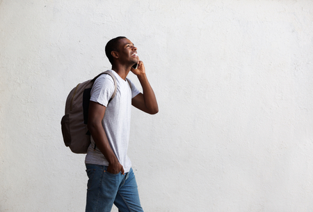 Side portrait of a happy student walking and talking on mobile phone