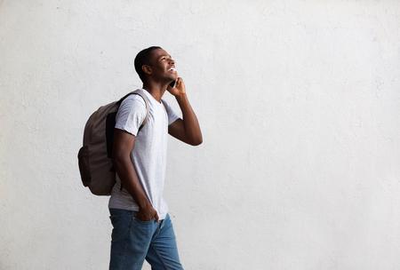 caminando: Retrato lateral de un estudiante caminar feliz y hablando por teléfono móvil