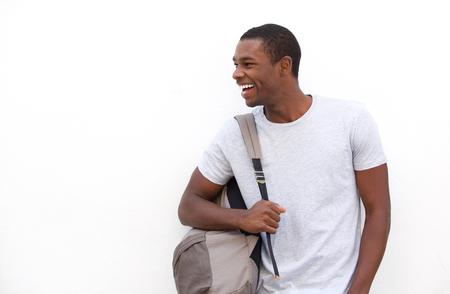 分離の白い背景の上にバッグと幸せなアフリカ系アメリカ人大学生の肖像画