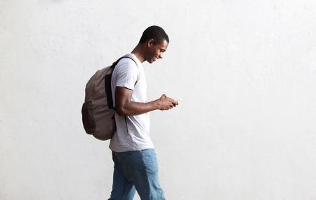 caminando: Vista lateral retrato de un estudiante afroamericano recorre con el bolso y el teléfono móvil