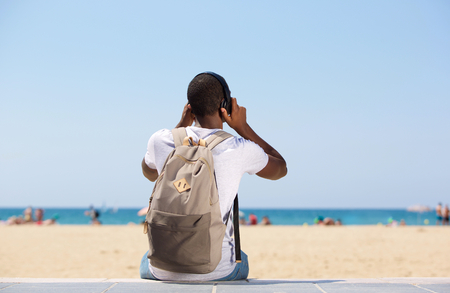 seashore: Young man sitting at the beach with bag and headphones Stock Photo