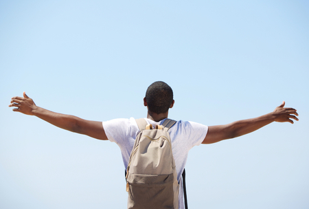 arm: Young black man standing with arms outstretched from behind