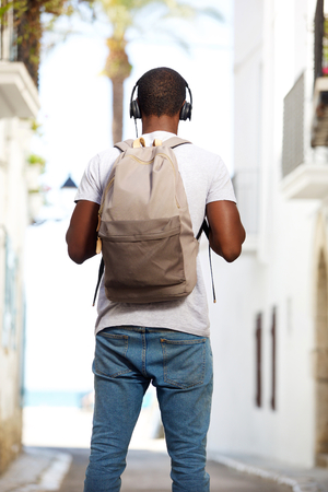 listening back: Portrait from behind of a young african american man with bag and headphones standing in the street Stock Photo