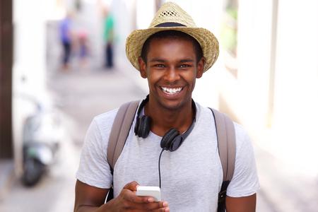Portrait eines glücklichen Reisenden zu Fuß in der Stadt mit Handy