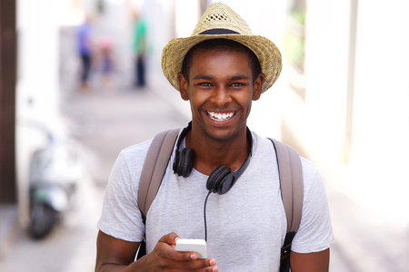 happy african: Portrait of a happy traveler walking in town with mobile phone
