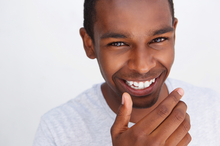 Close up portrait of a cute guy laughing with hand covering mouth