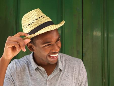 modelos hombres: Cerca de retrato de un hombre afroamericano de risa con el sombrero y mirando a otro lado