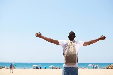 cielos abiertos: African American hombre joven de pie con los brazos abiertos en la playa extendi� Foto de archivo