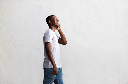 Side view portrait of a smiling african american guy walking and talking on mobile phone