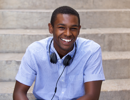 black guy: Close up portrait of a happy black guy sitting with headphones Foto de archivo