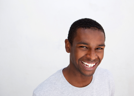 Close up portrait of a laughing black guy posing against white background