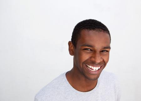 Schließen Sie herauf Portrait eines lachenden schwarzen Mann posiert vor weißem Hintergrund