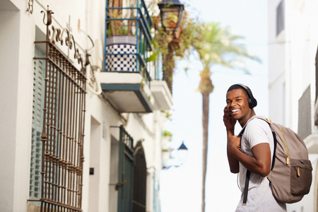 Portrait of a happy african american man traveling with bag and headphones