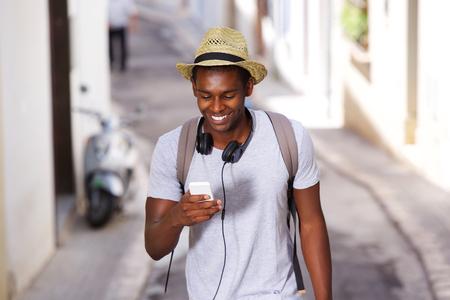 bonhomme blanc: Portrait d'un jeune homme afro-am�ricain heureux de marcher en ville avec un t�l�phone mobile