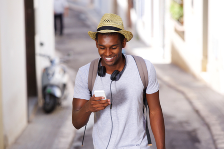 travellers: Portrait of a happy young african american man walking in town with mobile phone