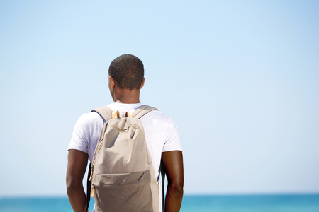Rear portrait of a black man standing with backpack by the sea