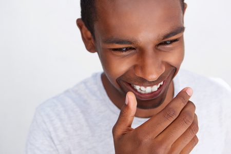 male models: Close up portrait of a young guy laughing with hand covering mouth