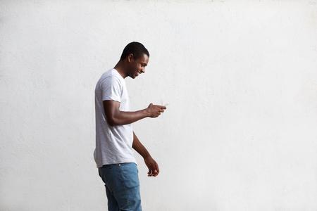 Side Porträt eines glücklichen Kerl zu Fuß und mit Handy