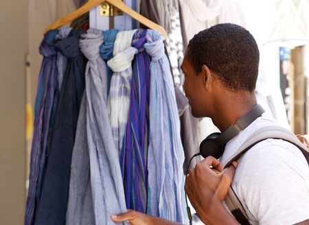 shopper: Portrait of a young black guy looking at clothes outside Stock Photo