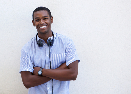 background person: Portrait of a smiling african american guy with headphones against white background