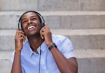 Close-up portret van een lachende jonge man luisteren naar muziek op de koptelefoon en het opzoeken van Stockfoto