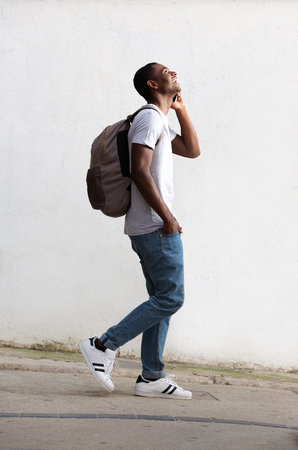 black student: Full length side portrait of a cheerful male student walking and talking on cell phone