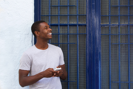 holding cell: Portrait of a happy guy holding mobile phone and looking away