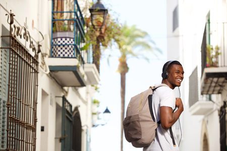 hombres negros: Portrait of a smiling young man traveling with bag and headphones